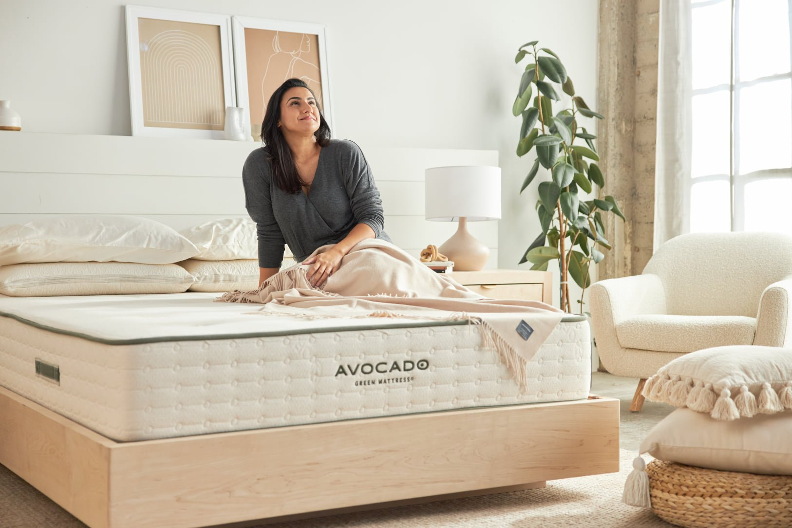 Sustainable furniture & home decor: woman sitting on unmade bed, neutral decor in background