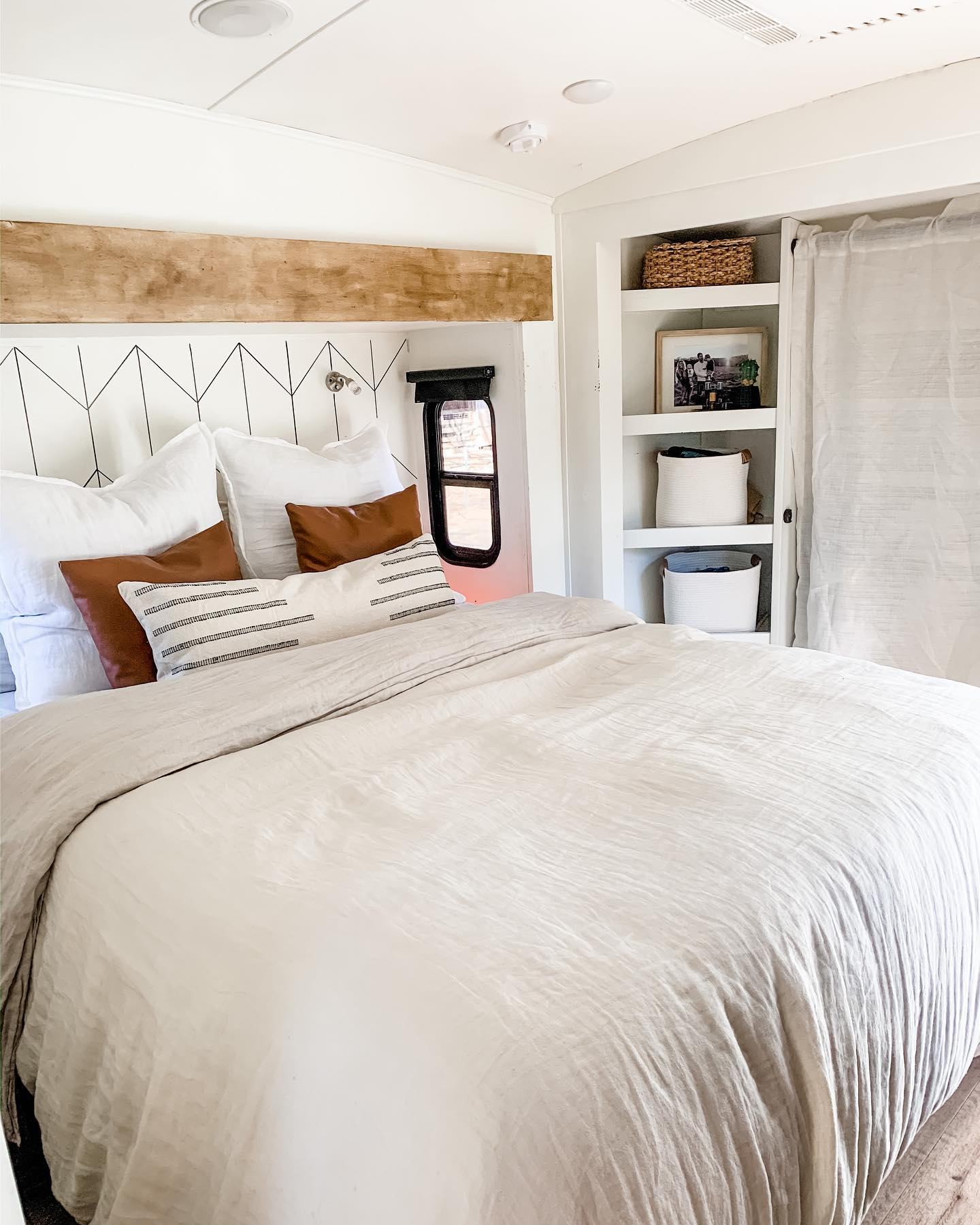 Sustainable furniture & home decor:  Off-white bedspread, with white and brown pillows and decor