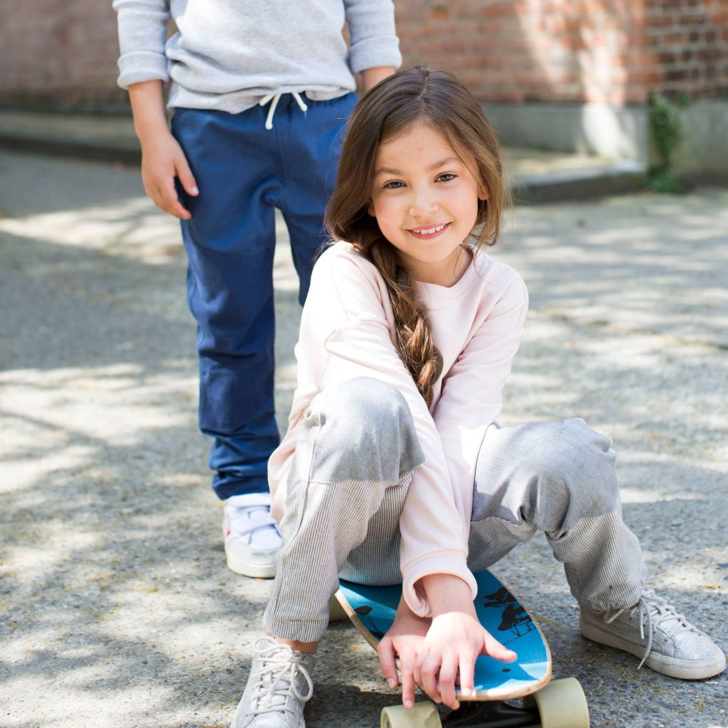 girl sitting on skateboard by Jackalo, a sustainable kids' clothing brand
