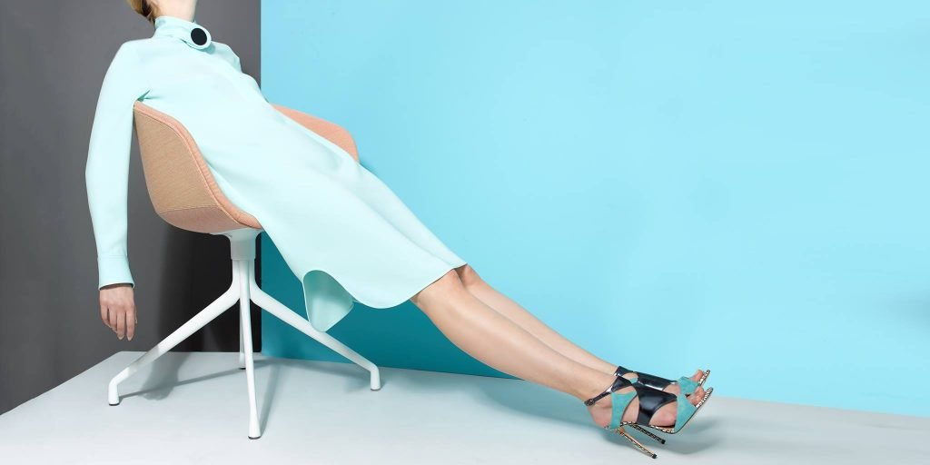 woman lounging in chair with legs outstretched, wearing Chelsea Paris sustainable shoes