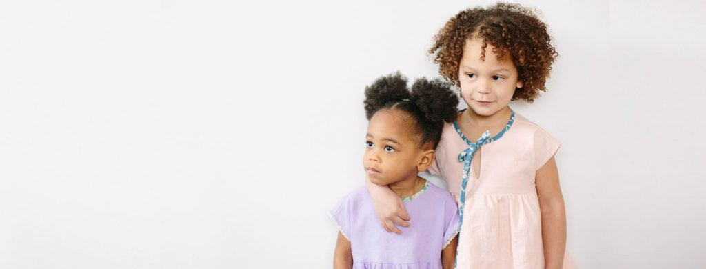 two kids embracing by BeyaMade, a sustainable kids' clothing brand