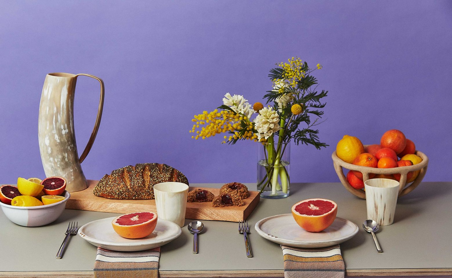 Sustainable furniture & home decor: Table arrangement including ruby red grapefruit, flowers, dark brown bread, and a bowl of fruit