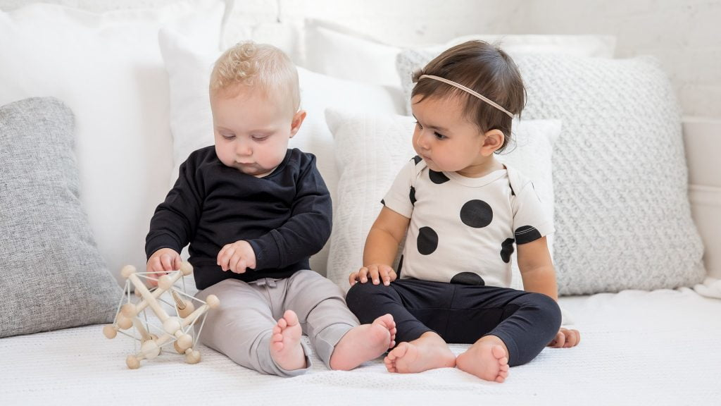 two children on neutral colour cushions by Colored Organics, a sustainable kids' clothing brand