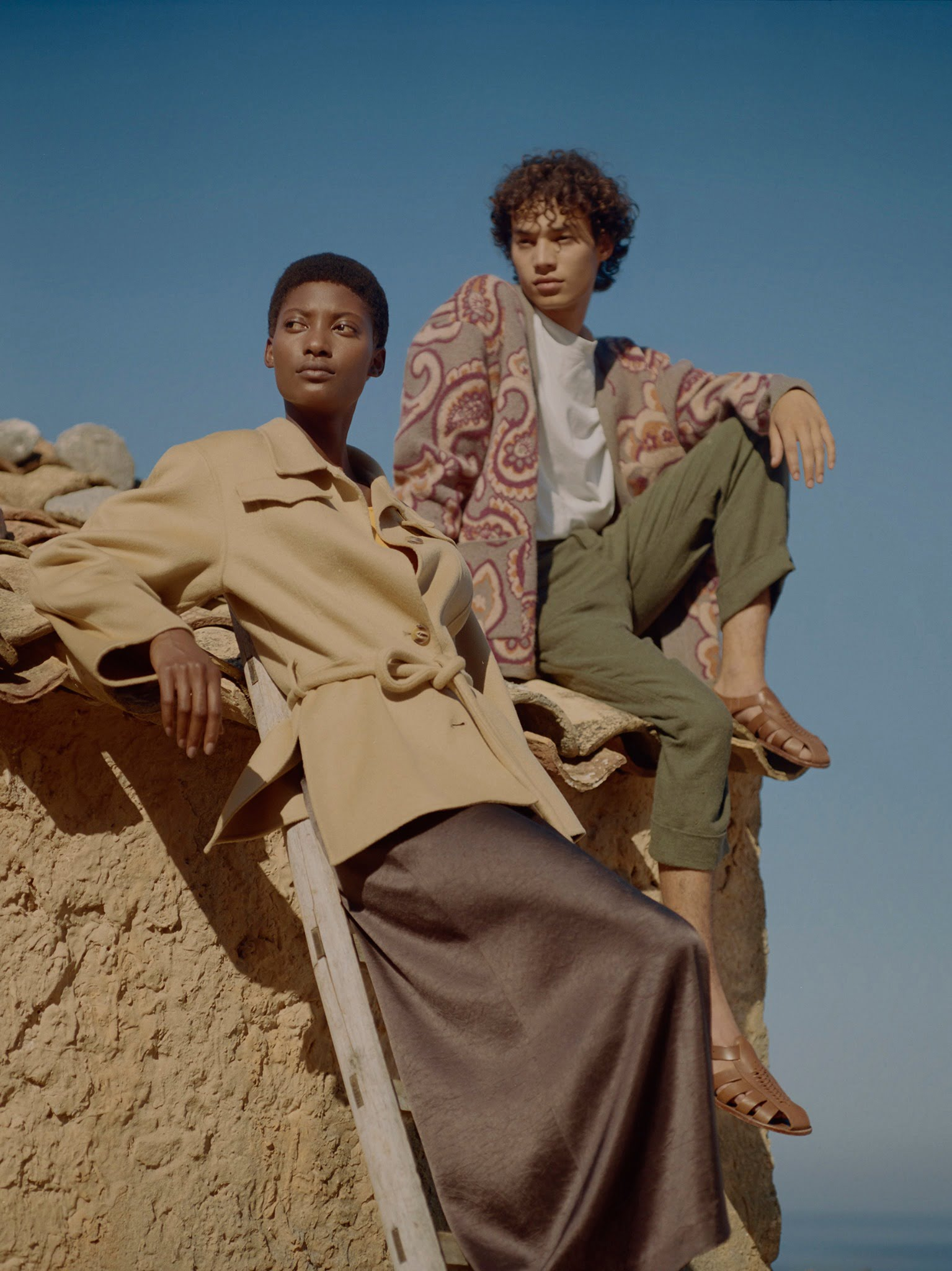man and woman sitting on rocks by Nanushka, a sustainable clothing brad