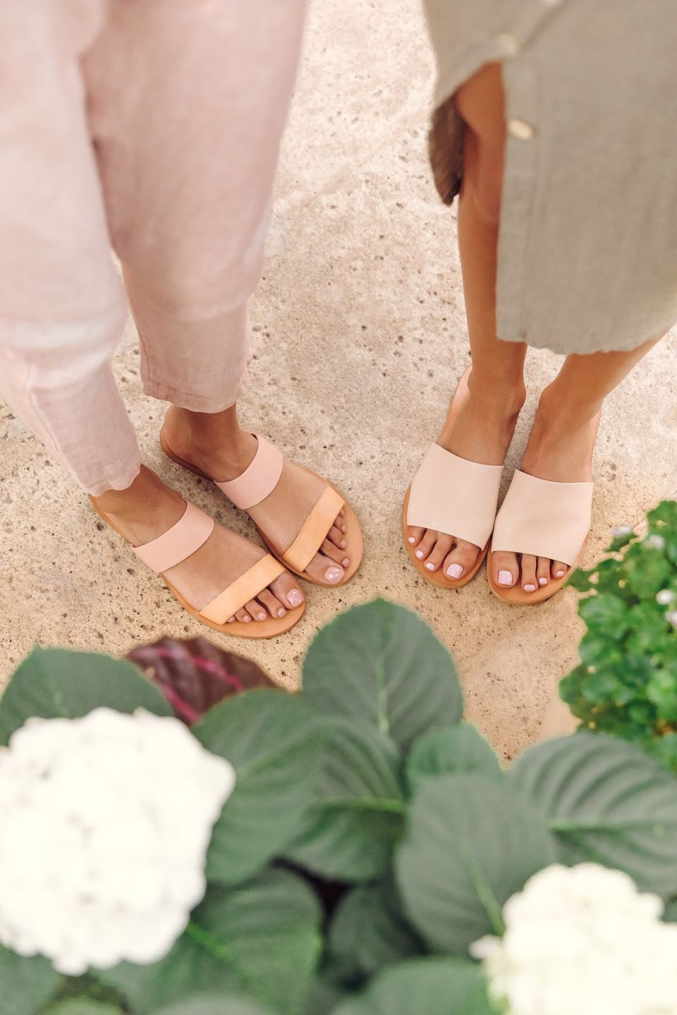 two ladies' feet wearing cream sandals by Cocobelle sustainable shoes brand