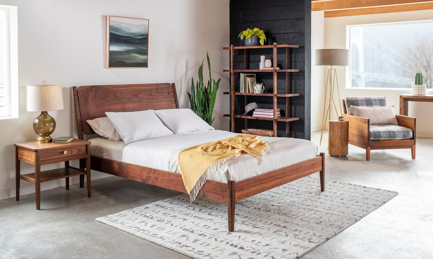 Wooden-framed bed, wooden sidetable, chair, and bookshelf, concrete floor, grey rug