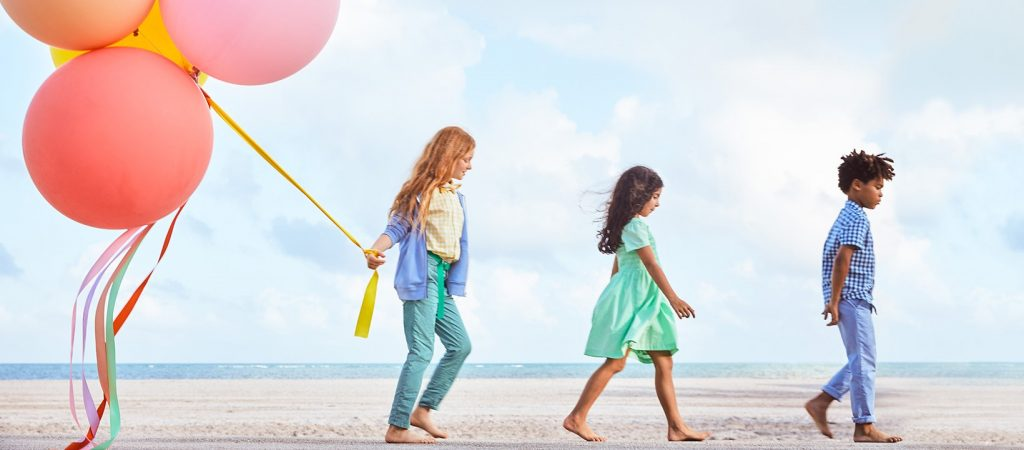 three kids walking on beach by Primary, a sustainable kids' clothing brand