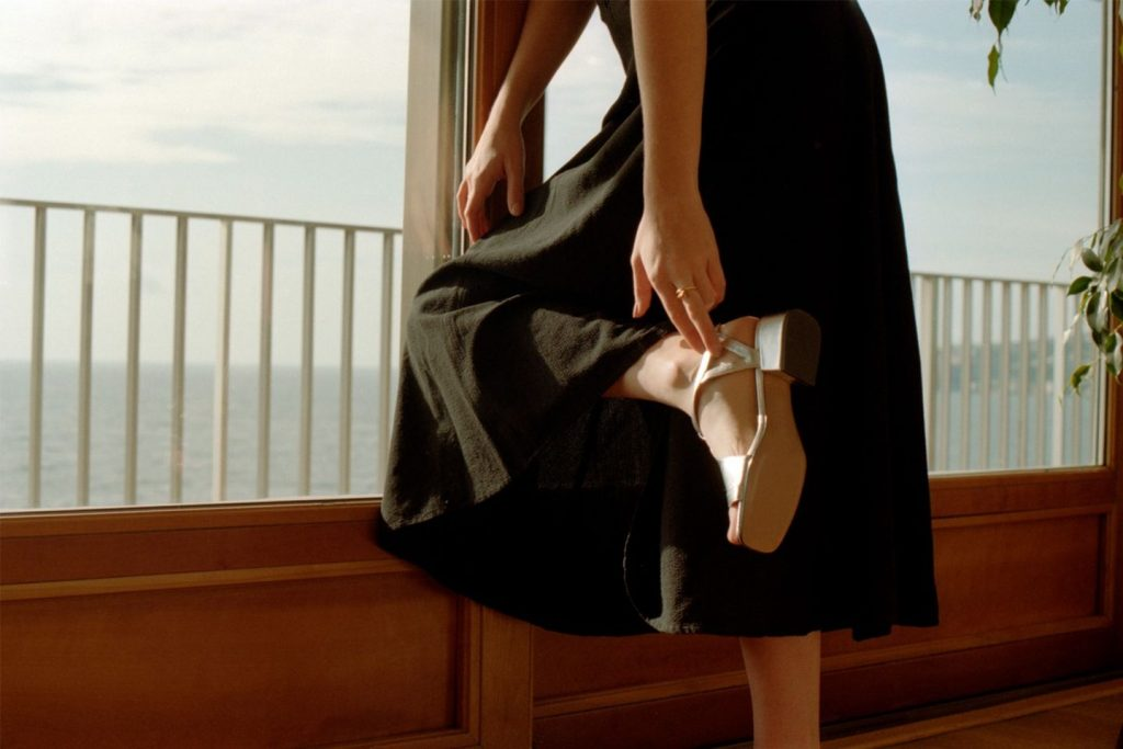 woman adjusted strap on slow fashion shoes