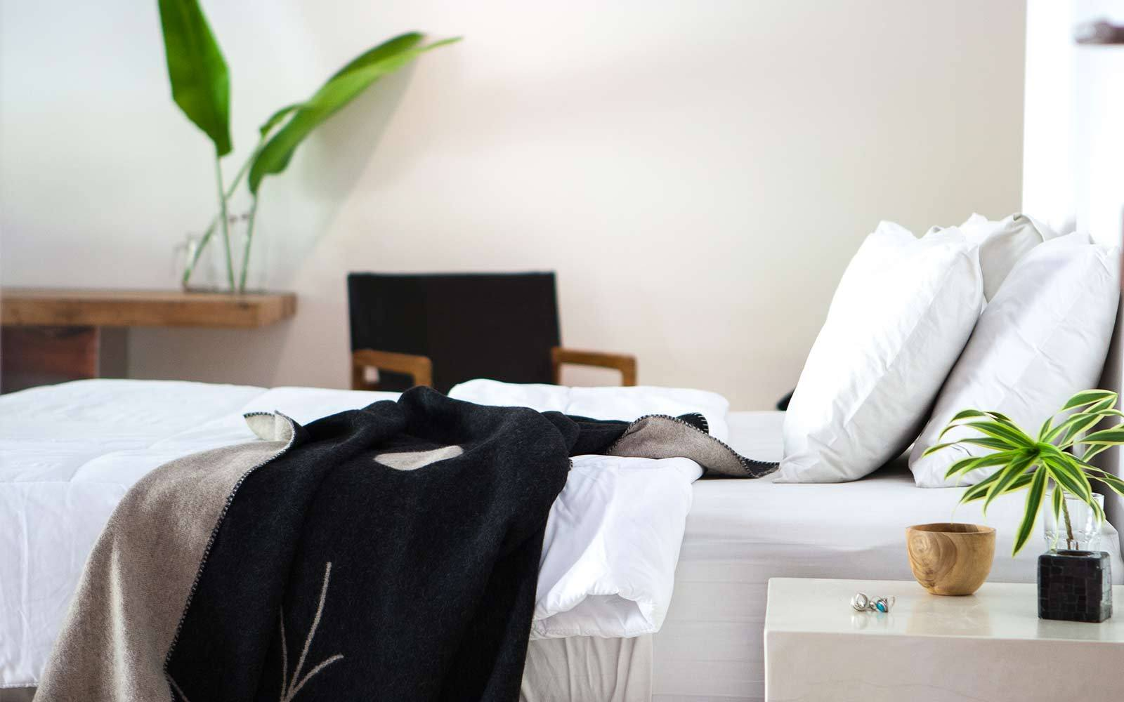 Sustainable furniture & home decor: White bed linens with black throw rug