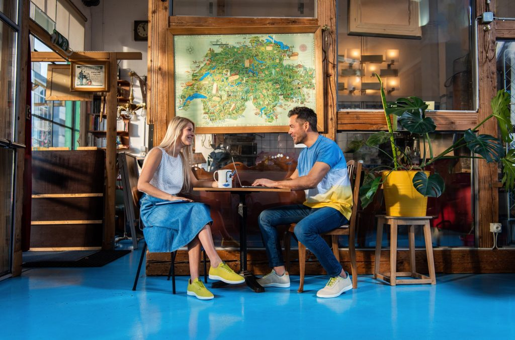 couple sitting in cafe wearing colorful ethical shoes