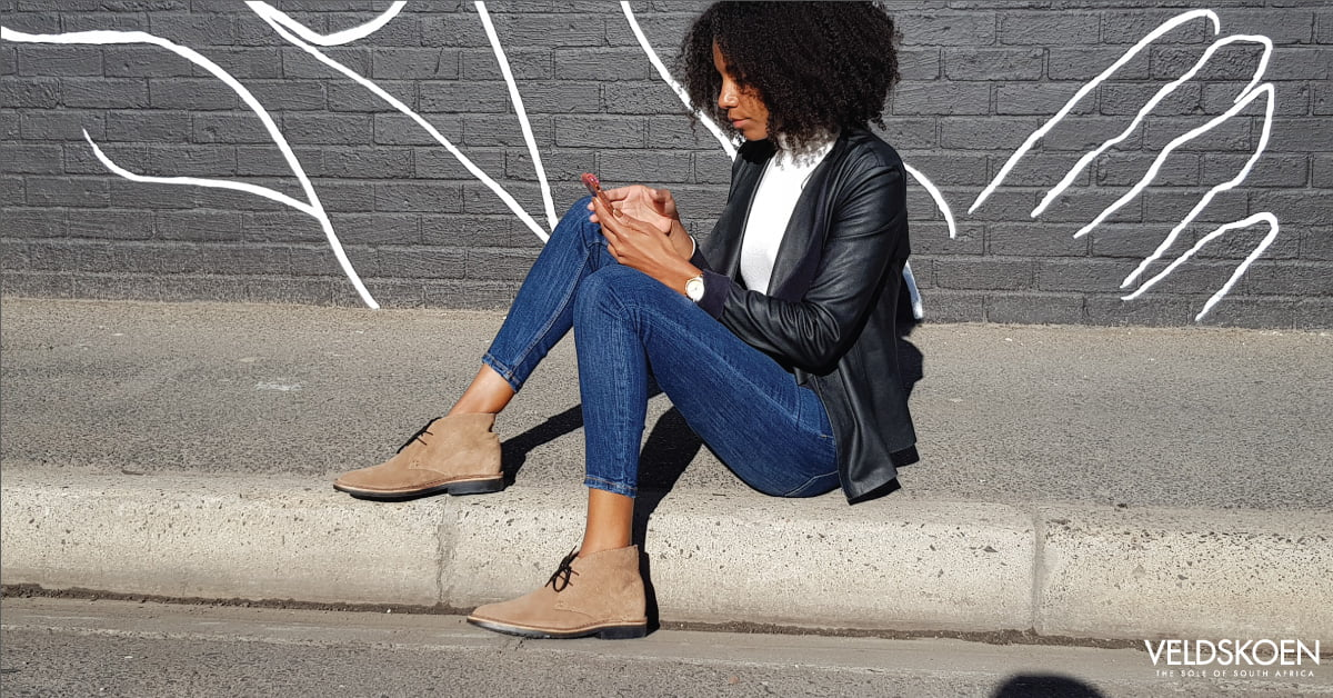 woman on phone sitting on sidewalk wearing brown handcrafted shoes