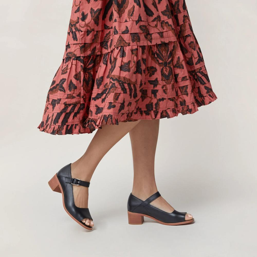 lady wearing peach coloured dress, and black shoes by Wilder, a ethical shoes brand