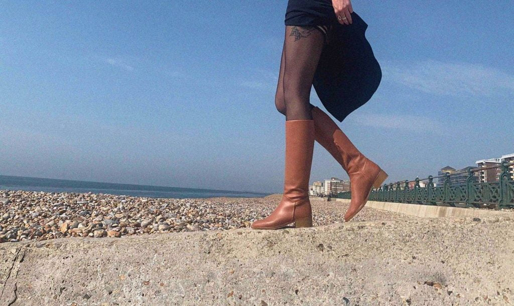 woman in tan leather boots walking on beach