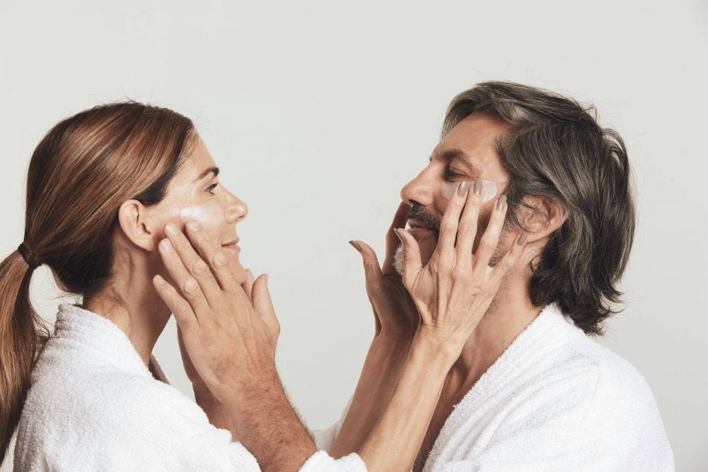 man and woman applying masks to each other's faces