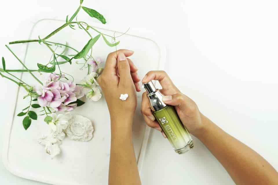 Hands holding Emani bottle, flowers
