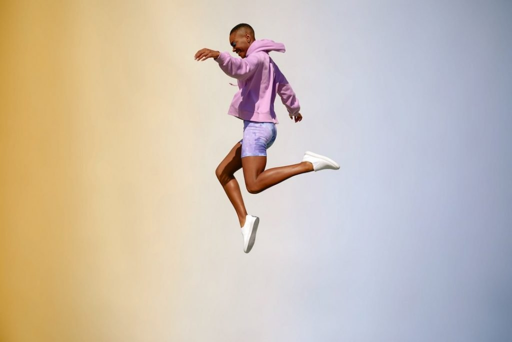 Man jumping in air with white vegan shoes