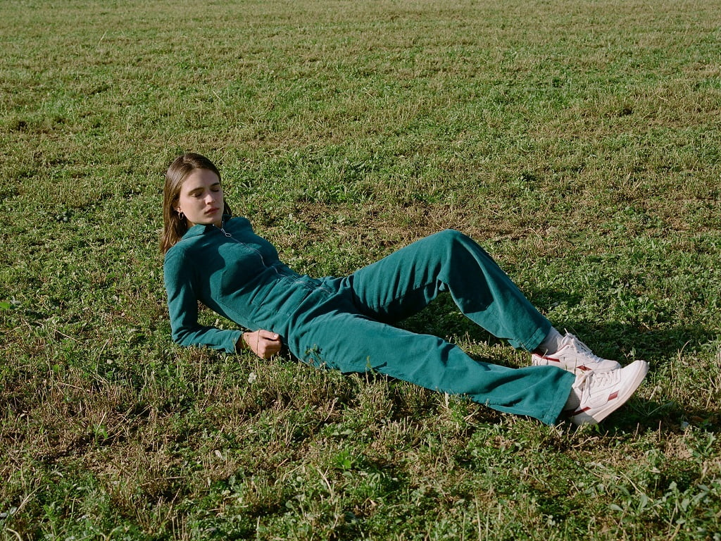 woman in green jumpsuit lying on grass