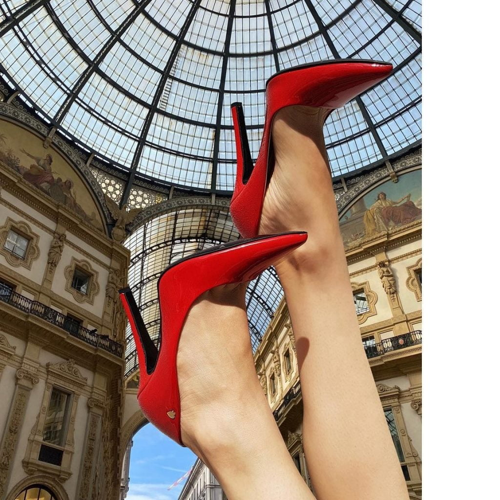 red vegan shoes pointing up towards renaissance ceiling