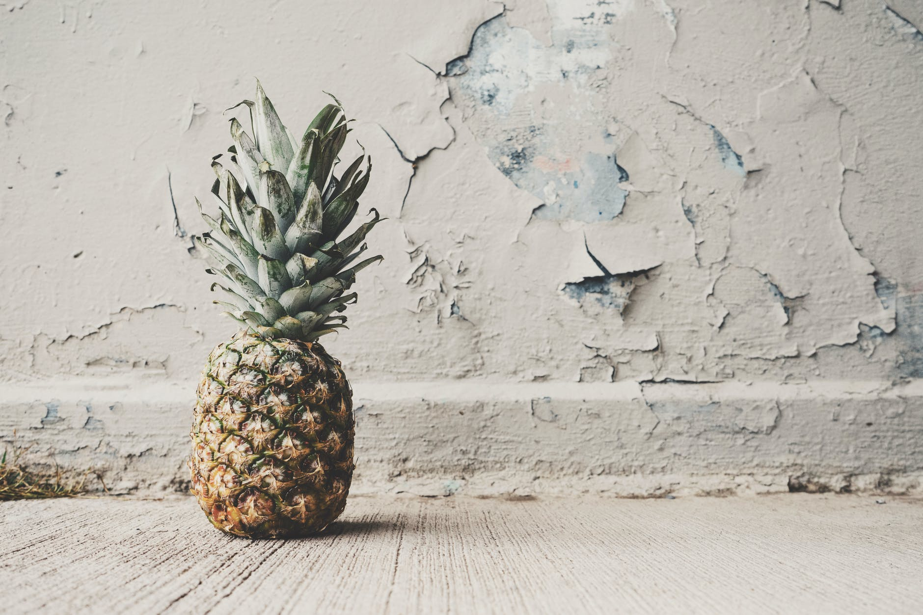 pineapple beside concrete wall