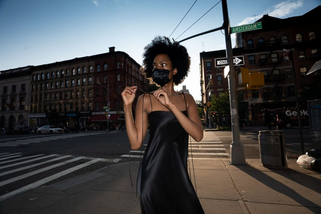 woman at intersection with black dress and black mask