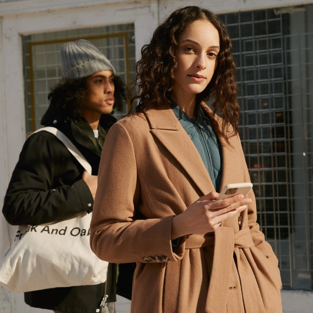 woman with tan coat holding phone