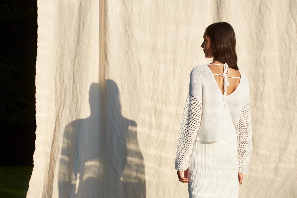 woman and shadow on cotton sheet