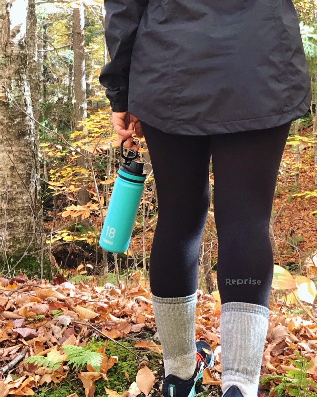 woman in leggings holding water bottle