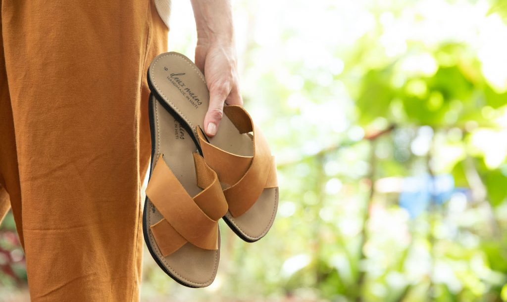 person holding two sandals with nature background