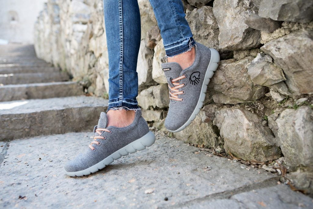 Giesswein sustainable sneakers worn by a woman sitting on a stone wall