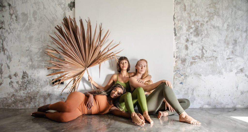 3 women sitting against a wall in sustainable activewear