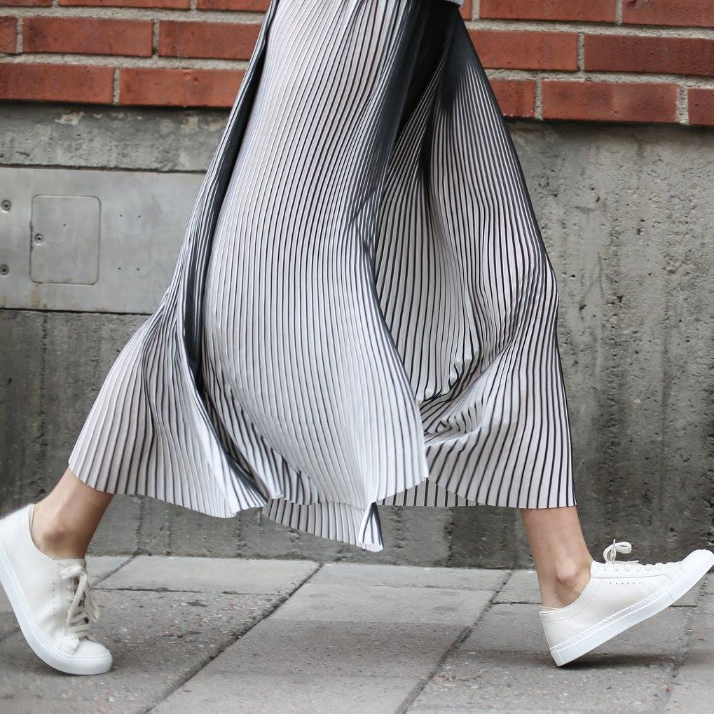 woman with white sneakers walking on pavement