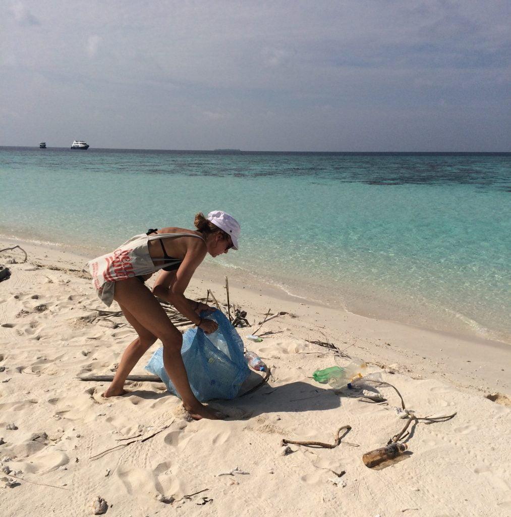 woman picking up trash at beach