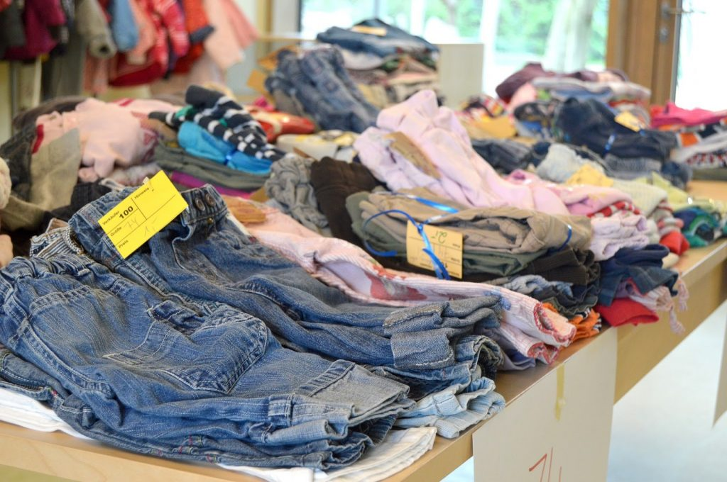 second hand clothes folded and displayed in a thrift shop