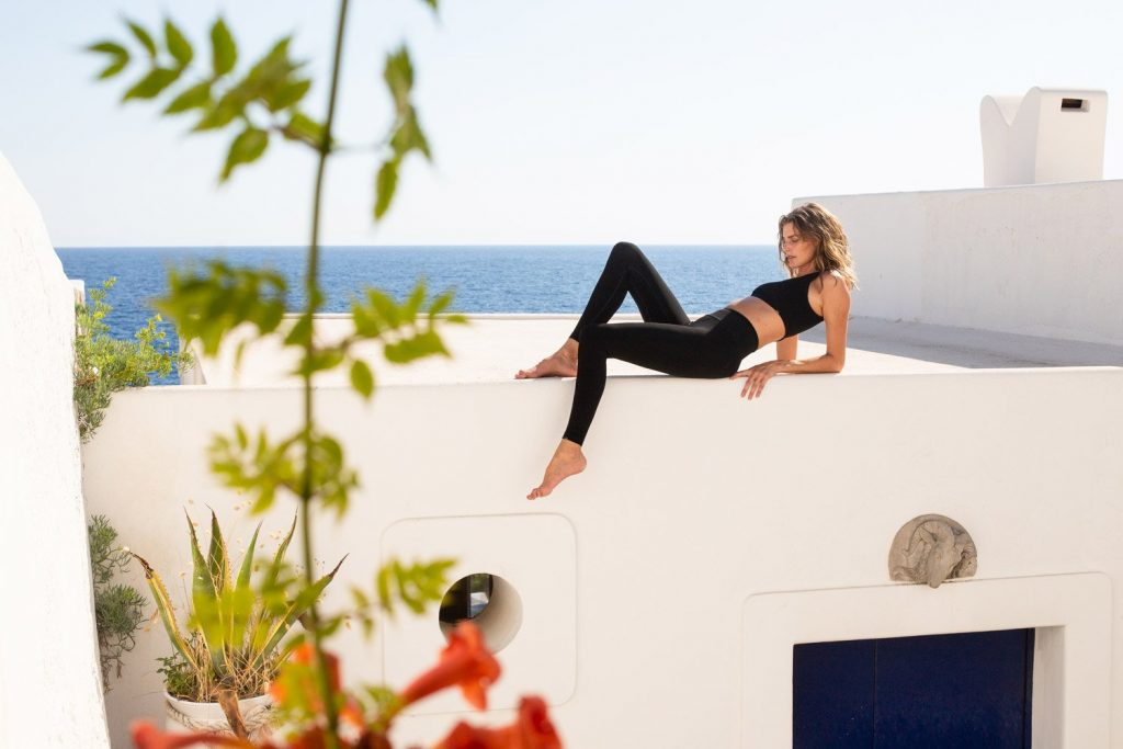 woman lounging on rooftop in the sun by Vyayama, a sustainable activewear brand