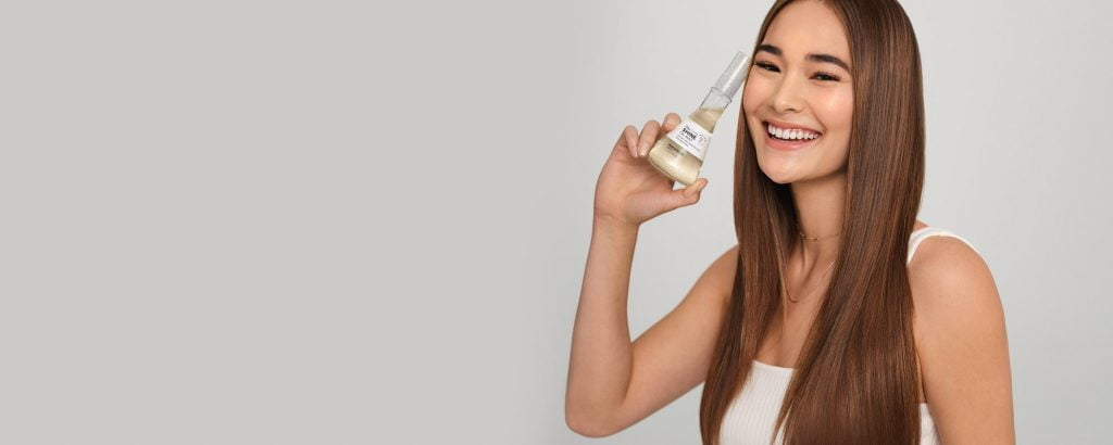 woman with shampoo bottle