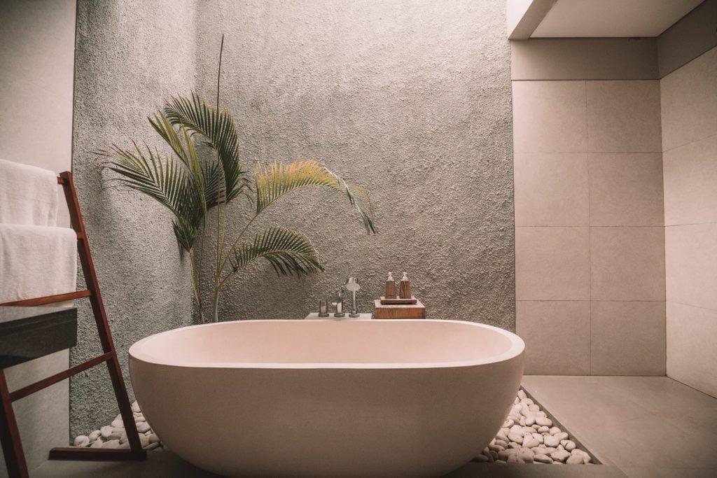 free standing bath in stone bathroom with fern