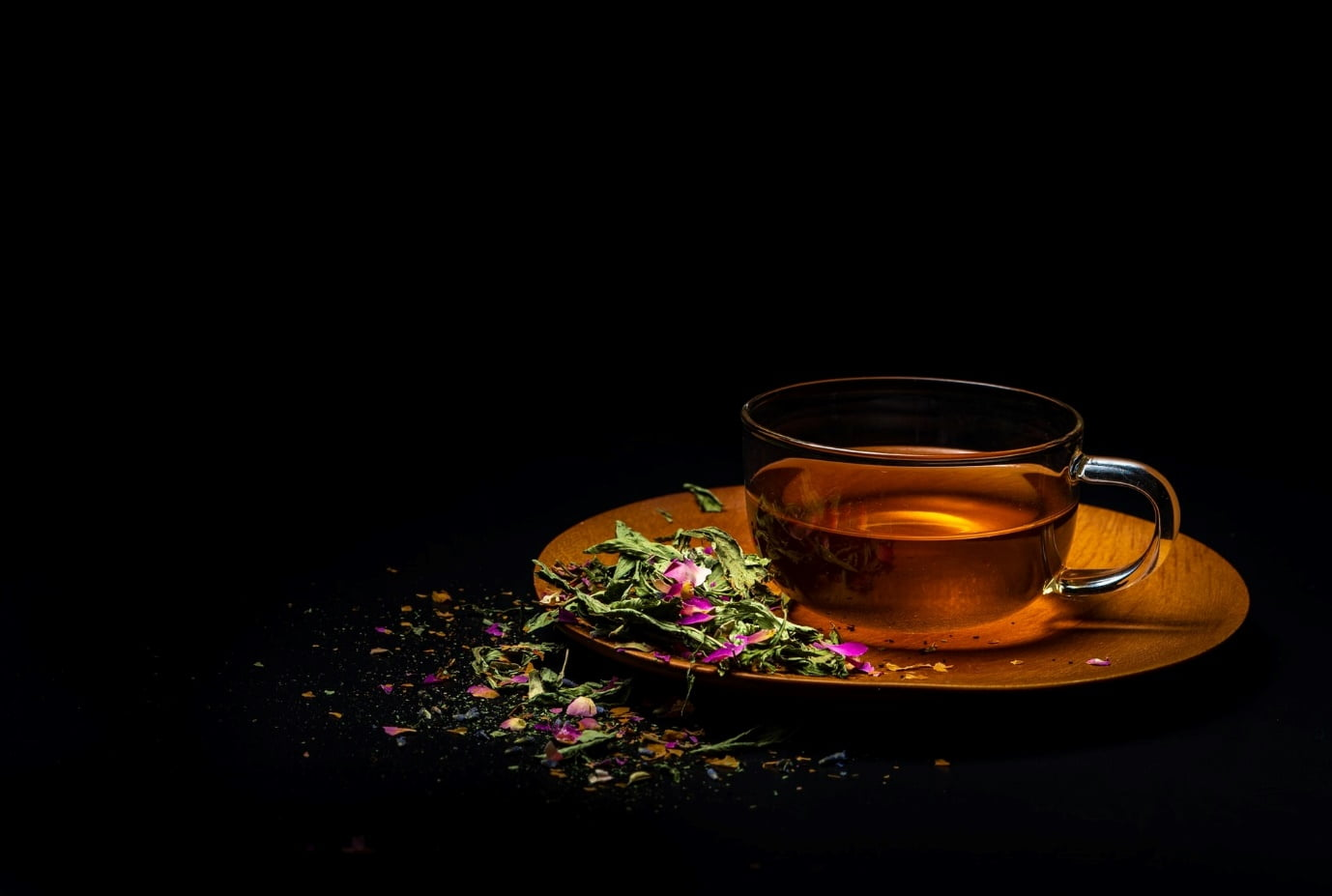 Tea cup with leaves on black background