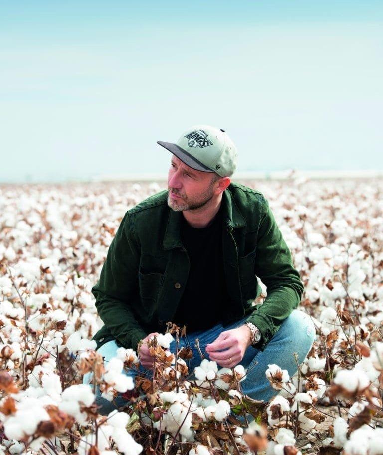 man crouching in cotton field under blue sky
