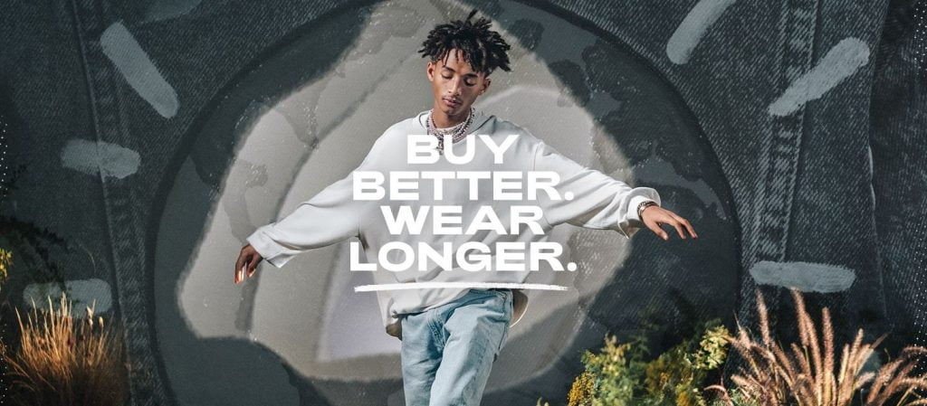 """man in jeans and white jumper with words """"buy better wear longer"""""""