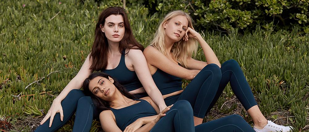 Three women outdoors wearing sustainable activewear