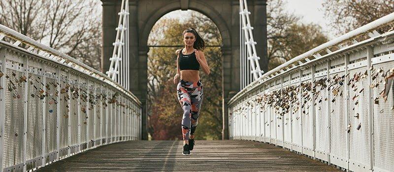 Woman running on bridge in leggings