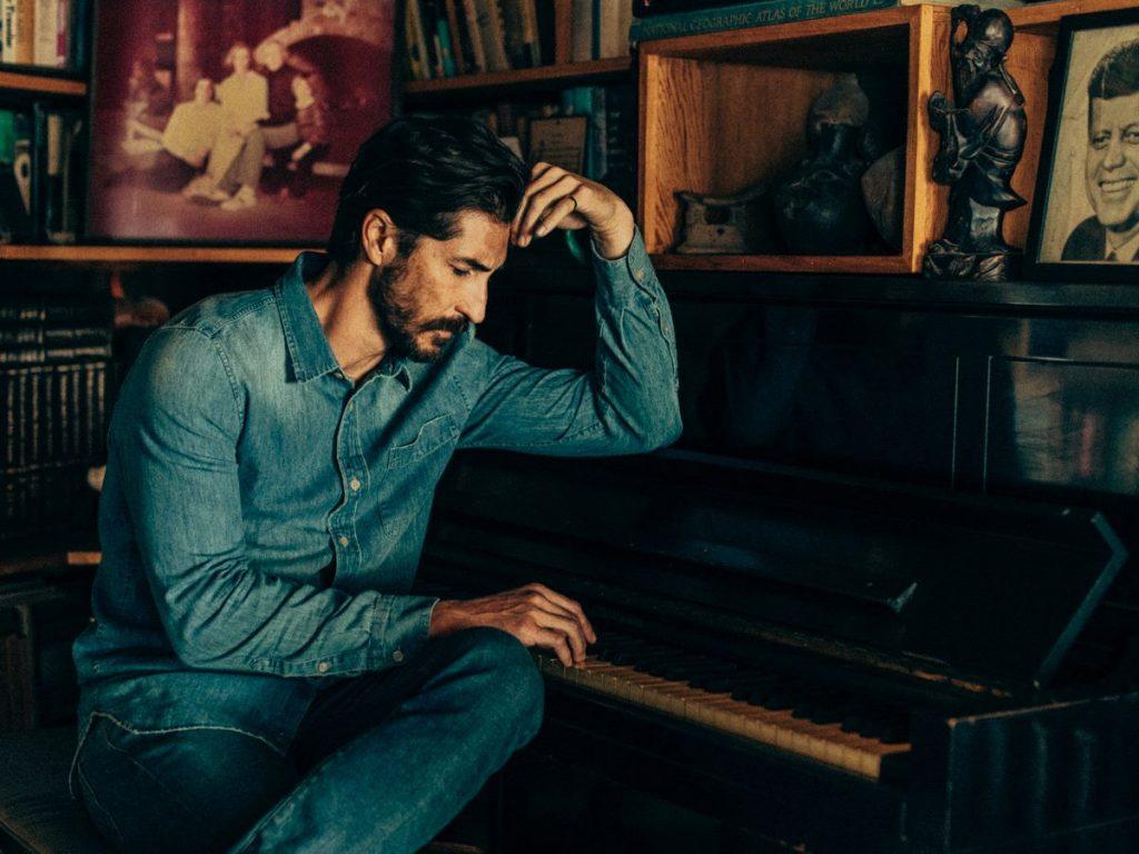 man wearing denim sitting at piano