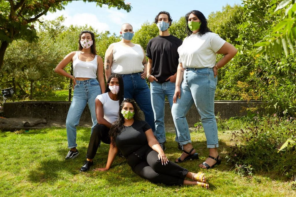 6 different sized people standing in garden in masks