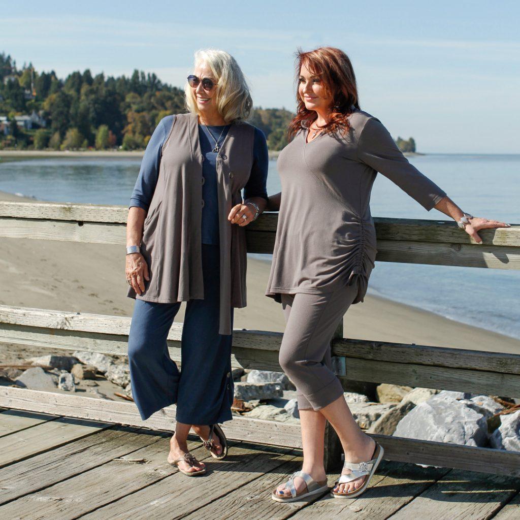 two women standing on boardwalk by beach