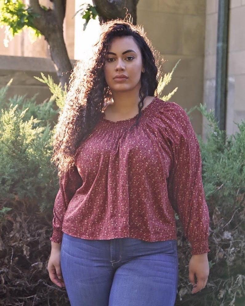 dark-haired plus-sized woman in garden