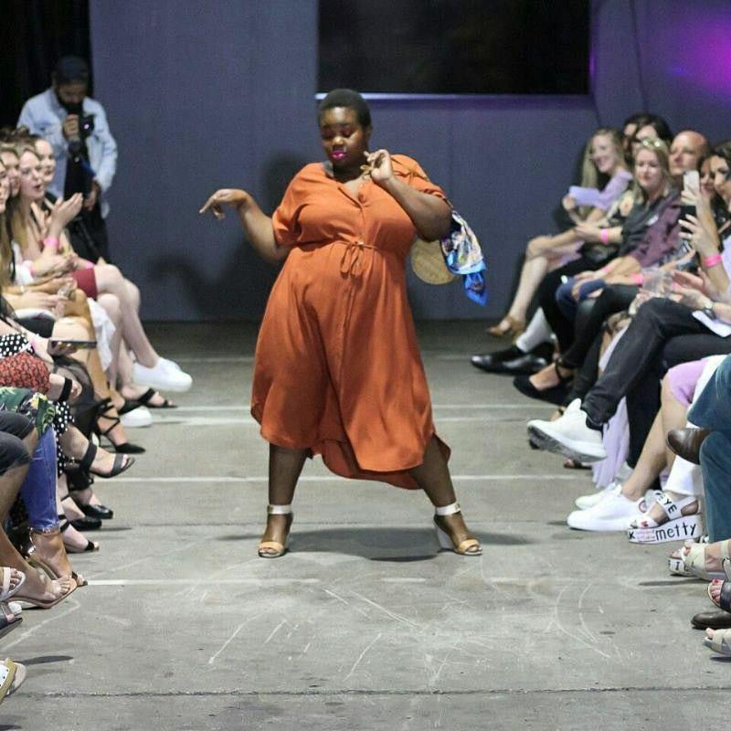 Size Inclusive woman in orange dress on runway
