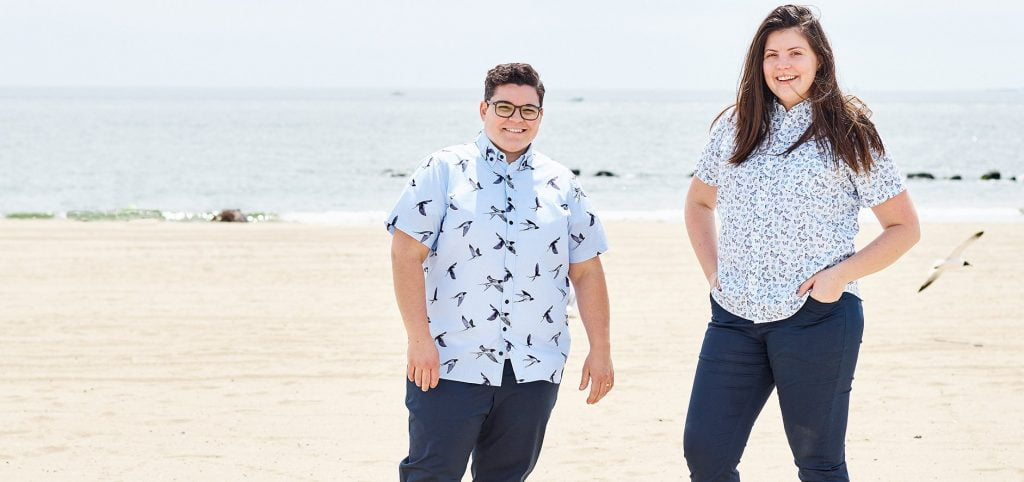 two people in short sleeved shirts at the beach