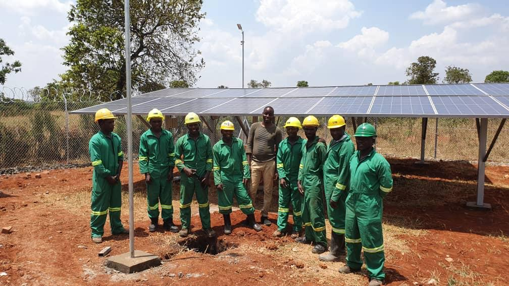 group of workers before solar panels