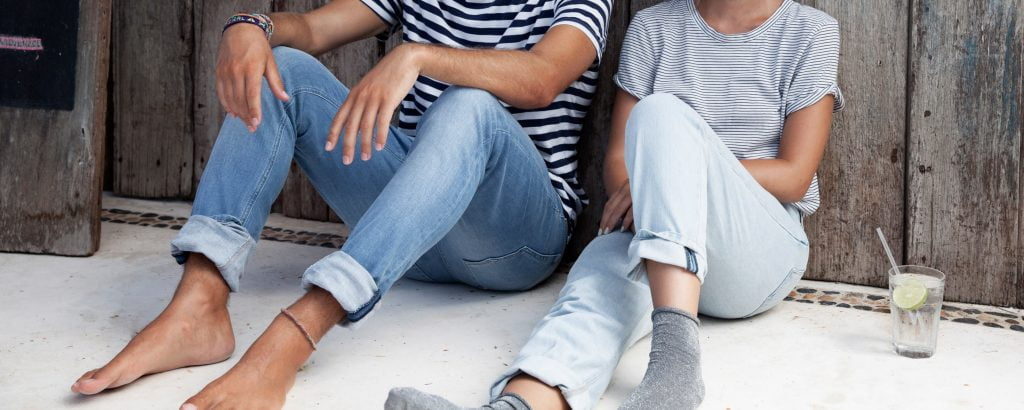 two people in jeans sitting against wooden wall