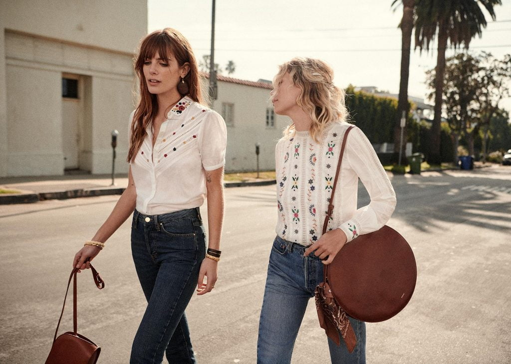 two women walking in white tops and jeans